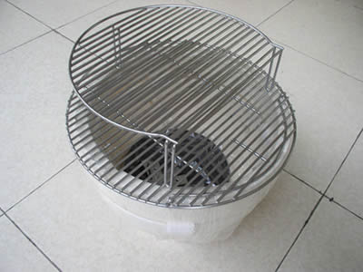 A circle stainless steel welded mesh grill is standing on a circle container on the floor.