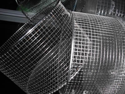 Two medium size deep circular stainless steel welded mesh baskets cross on the table.