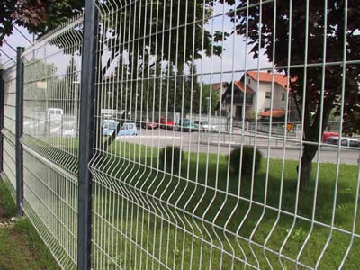 A stainless steel welded mesh fence for lush grass and luxuriant trees.