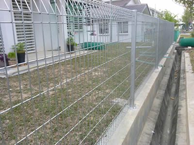 A row of residential building separated from the outside by stainless steel welded mesh fence, between them is a space.