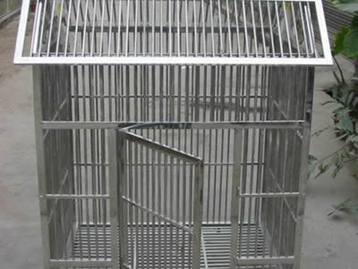 A medium size stainless steel welded mesh cage lays on the floor, it has a triangular roof and the door is open.