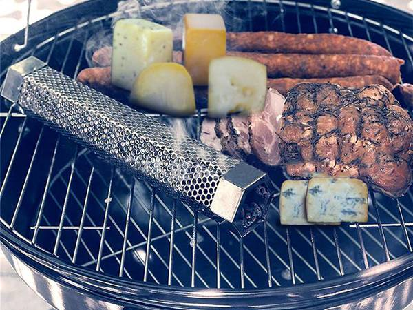 A pellet smoker tube is placed next to the grilled food.