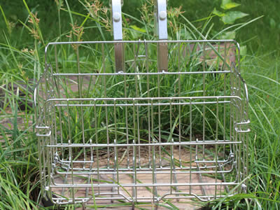 A small size stainless steel welded mesh bicycle basket with two short hooks put on the grassland.