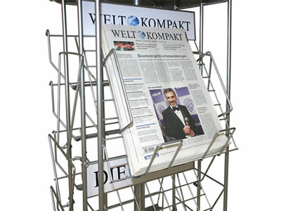 A bookshelf made of stainless steel welded mesh stand on the floor, some English magazine put on it.