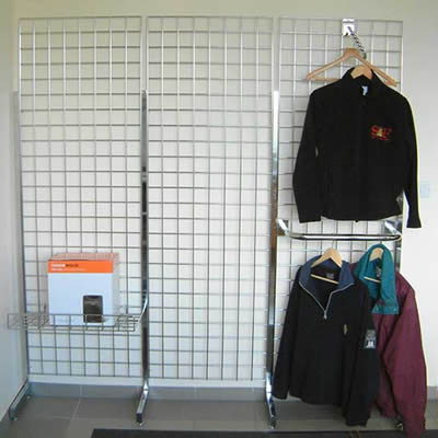 A stainless steel welded mesh grid wall for clothes at the corner, some coats are hung on it, a box put on the horizontal shelf.