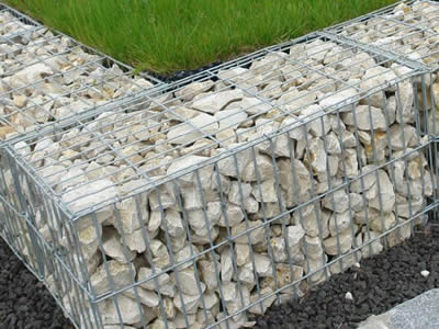 Two neighboring low stainless steel welded mesh gabion baskets perpendicular to another gabion basket for soil stabilization.