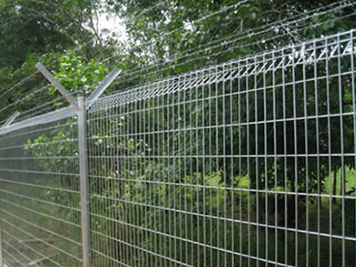 A large greenbelt is separated from the outside pathway with a very long stainless steel welded wire mesh.