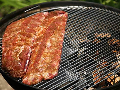 Two piece of meat lay on the round stainless steel welded mesh grills, with some firewood in the container under the grill.