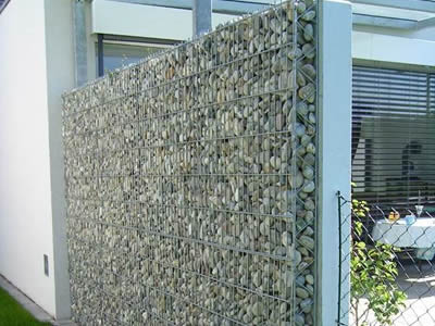 A high stainless steel welded mesh gabion serve as a wall dividing the garden into two place.