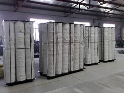 Four pallets with stainless steel welded mesh rolls packaged with waterproof stand on the floor.